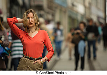 A young blond woman in a red blouse posing standing on the street.