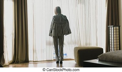 A young blonde in a seductive striped suit is standing by the window