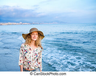 A young blondy girl in a sunhat sitting on a bench - A young...