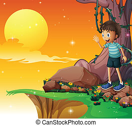 A young boy above the rocks near the cliff