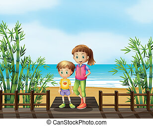 A young boy and a girl at the bridge near the beach