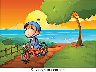 A young boy biking near the river