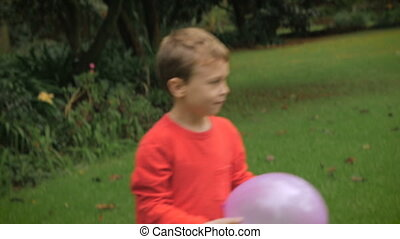 A young boy brings a balloon to his mother outside in a yard - slow mo