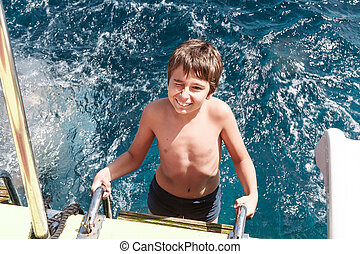 A young boy climbs the stairs from the sea