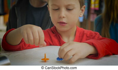 A young boy in red shirt playing with spinning tops on a table