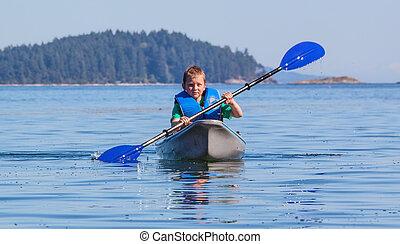 young boy kayaking