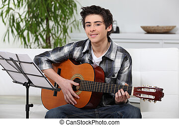 A young boy learning guitar.