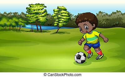 A young boy playing soccer near the river
