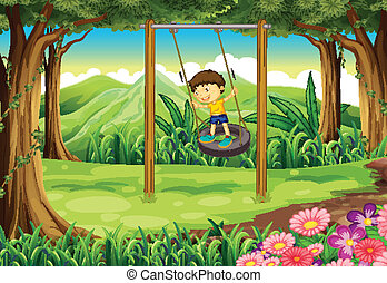 A young boy playing with the tire swing