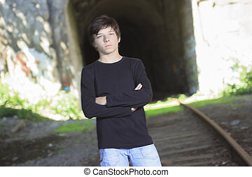 A young boy posing at the railroad