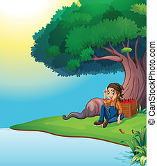 A young boy relaxing under the tree