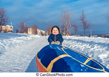 A young boy ribs drags a toy tubing for riding on a hill. In the winter in the city in fresh air. Strong and powerful guy.