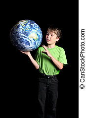 A young boy student looks at the world with amazement and curiosity against a dark background. Slight motion in left hand