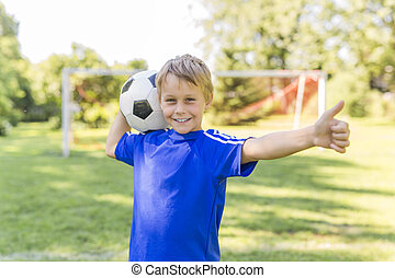 Young boy with soccer ball on a sport uniform