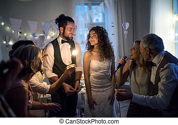 A young bride and groom with other guests dancing and singing on a wedding reception.
