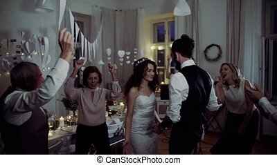 A young bride and groom with other guests dancing on a...