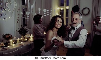 A young bride dancing with grandfather and other guests on a...