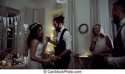 A young bride, groom and guests dancing on a wedding...