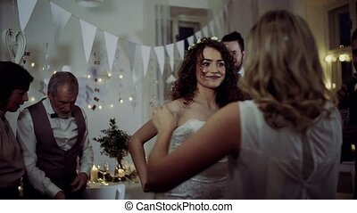 A young bride with other guests dancing and singing on a...