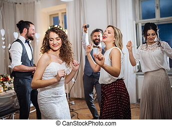 A young bride with other guests dancing on a wedding reception.