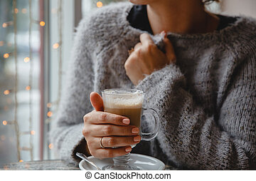 A young brown-haired woman in a warm jacket is sitting in a cafe at a table by the window and holding a glass of coffee