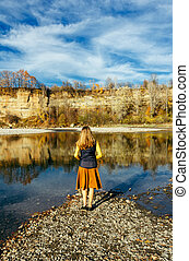 a young brunette girl with loose hair stands on the river Bank against the background of rocks on an autumn Sunny day, view from the back