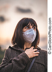 A young brunette with a mask on a sunset. First walks of the uncontrolled Covid-19 pandemic