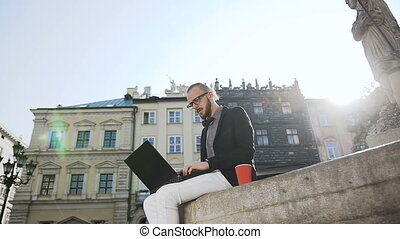 A young business man in glasses with a beard work on a computer in the city and drinks coffee