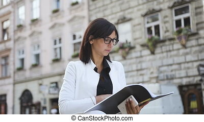 A young business woman goes to the city and looks at the documents