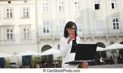 A young business woman in glasses work on a computer in the city and drinks coffee