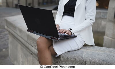 A young business woman in glasses work on a computer in the city