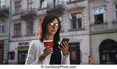 A young business woman in the glasses goes around the city,talks on the phone and drinks coffee