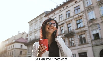 A young business woman walking around the city,talking on the phone and drinking coffee
