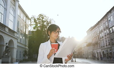 A young business woman wearing glasses walking around the city and drinking coffee while looking at documents