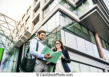 A young businessman and businesswoman standing in front of a building, looking at notes.