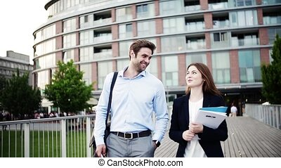 A young businessman and businesswoman walking on a bridge.