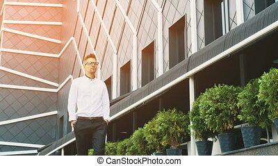 A young businessman dressed in business clothes stands at the office.