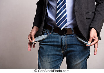A young businessman in a business suit showing his empty pockets. Financial difficulties, bad economy, no money concept.