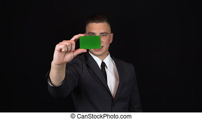 A young businessman in a suit holds a bank card in hand. Isolated black background. Chromakey green card. 4k