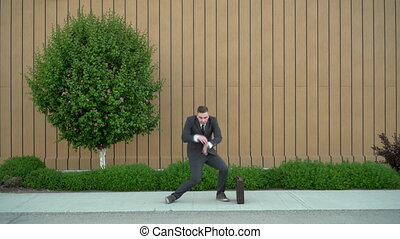 A young businessman in a suit is dancing. Modern youth flex. A man dances with joy against the background of a building with a flowerbed. 4k