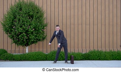 A young businessman in a suit is dancing. Modern youth flex. A man dances with joy against the background of a building with a flowerbed. Slow motion. FHD