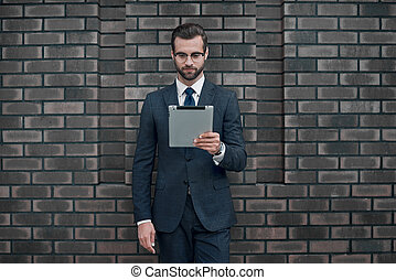 A young businessman in glasses and an expensive suit, holds a tablet in his hands