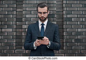 A young businessman in glasses and an expensive suit, works on a smarphone in his hands