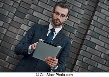 A young businessman in glasses and an expensive suit, works on a tablet in his hands