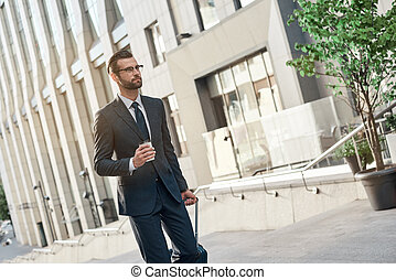 A young businessman spectacled climbs the stairs with coffe and suitcase