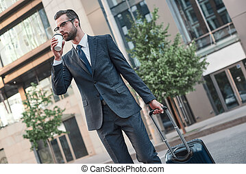 A young businessman spectacled crosses road with coffe and suitcase