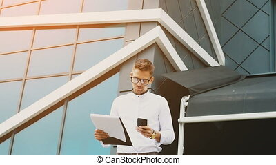A young businessman stands at the office with a folder of documents in his hands.