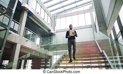 A young businessman walking down the stairs in office...