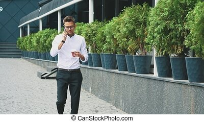 A young businessman wearing business clothes and glasses goes to work.