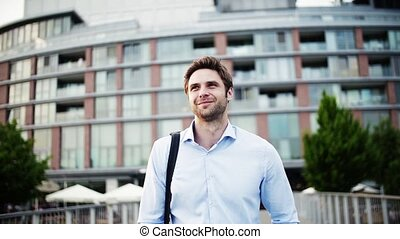 A young businessman with a bag walking on a bridge. - A...